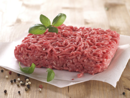 Minced meat on butcher paper with basil and pepper, selective focus